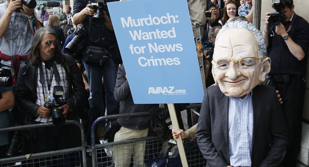 A protester wearing a Rupert Murdoch mask is photographed by media outside parliament in London, Tuesday, July 19, 2011.