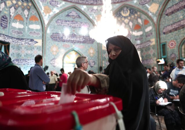 An Iranian woman casts her ballot for the presidential elections at a polling station in Tehran on May 19, 2017