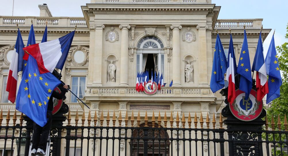 A worker arranges European flags alongside French national flags on the railings outside the Ministry of Foreign Affairs in Paris (File)