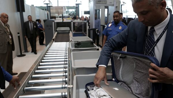 A TSA official removes a laptop from a bag for scanning using the Transport Security Administration's new Automated Screening Lane technology at Terminal 4 of JFK airport in New York City, U.S., May 17, 2017 - Sputnik International