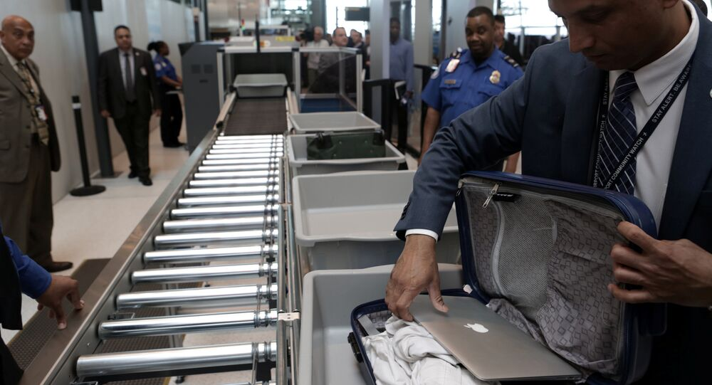 A TSA official removes a laptop from a bag for scanning using the Transport Security Administration's new Automated Screening Lane technology at Terminal 4 of JFK airport in New York City, U.S., May 17, 2017