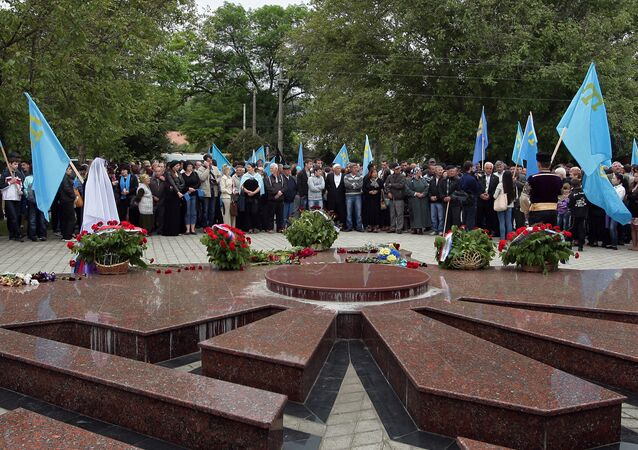 People conducting a prayer service at the monument to deported peoples in Simferopol during events marking the 70th anniversary of the deportation of the Crimean Tatars