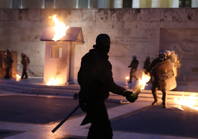 A masked demonstrator prepares to throw a petrol bomb to riot police outside the parliament building as Greek lawmakers vote on the latest round of austerity Greece has agreed with its lenders, in Athens, Greece, May 18, 2017.