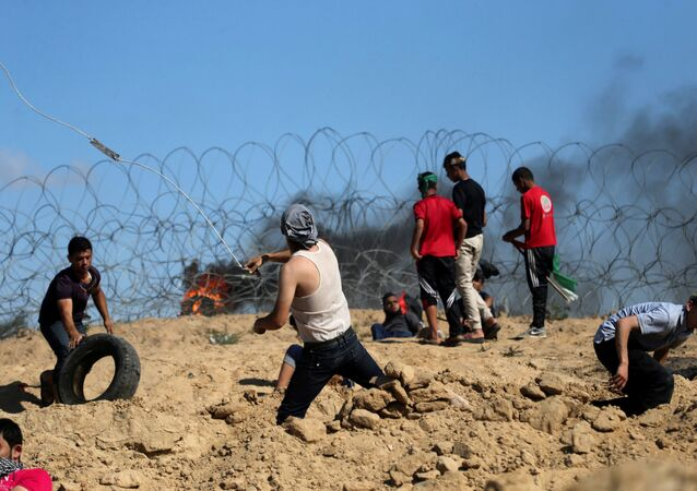 Palestinian protesters hurl stones at Israeli troops following a protest against the blockade on Gaza, near the border between Israel and Central Gaza Strip May 19, 2017