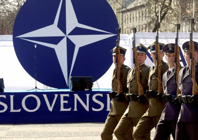 Members of a honor guard present arms in front of the NATO logo during a ceremony to mark the country's entry into the military alliance on Friday, April 2, 2004 in Bratislava
