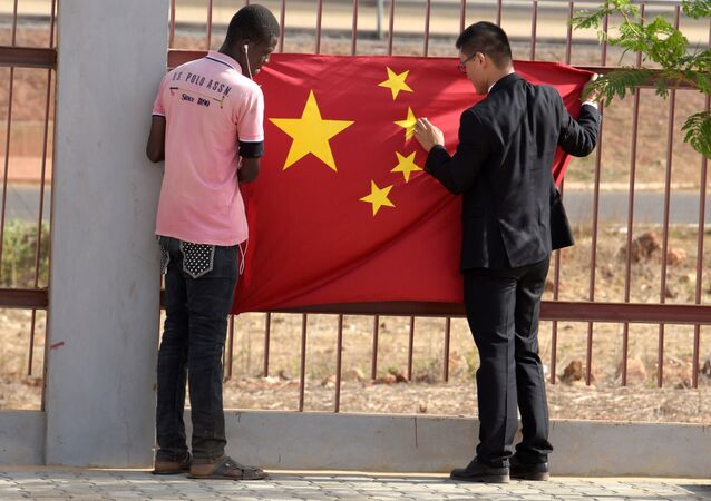 A Senegalese worker and a Chinese man put a Chinese flag in Diamniadio district in Dakar on May 7, 2017 during the visit of Chinese vice president Li Yuanchao (not seen)