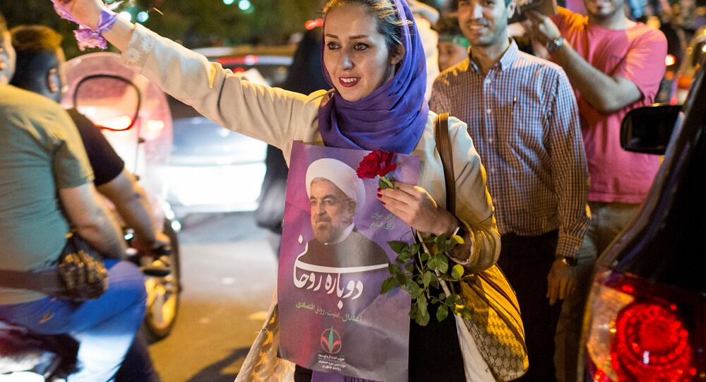 A woman holds a poster of Iranian President Hassan Rouhani during a campaign rally in Tehran, Iran, May 17, 2017