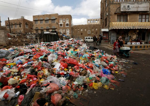 A girl pushes a wheel cart with water jerrycans past a pile of rubbish bags on a street during a strike by garbage collectors demanding delayed salaries in Sanaa, Yemen May 8, 2017