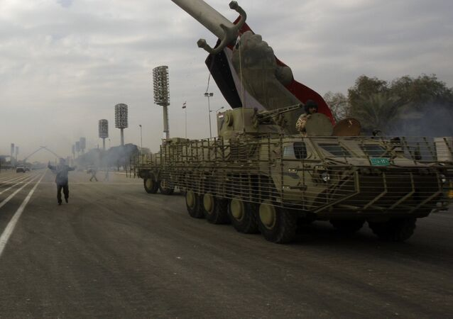 Iraqi army military vehicles march under the victory Arch landmark during a parade to mark the 91st Army Day in Baghdad on January 6, 2012, weeks after US troops completed their pullout