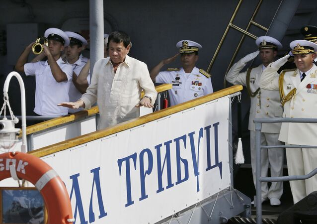Russian Navy and a Philippine officer salute as Philippine President Rodrigo Duterte alights from the Russian anti-submarine Navy vessel Admiral Tributs in Manila, Philippines on Friday, Jan. 6, 2017