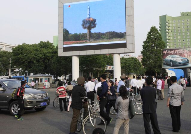 People watch a news broadcast on the launch of the solid-fuel Pukguksong-2 missile on a screen in front of the railway station in Pyongyang, North Korea, Monday, May 22, 2017.