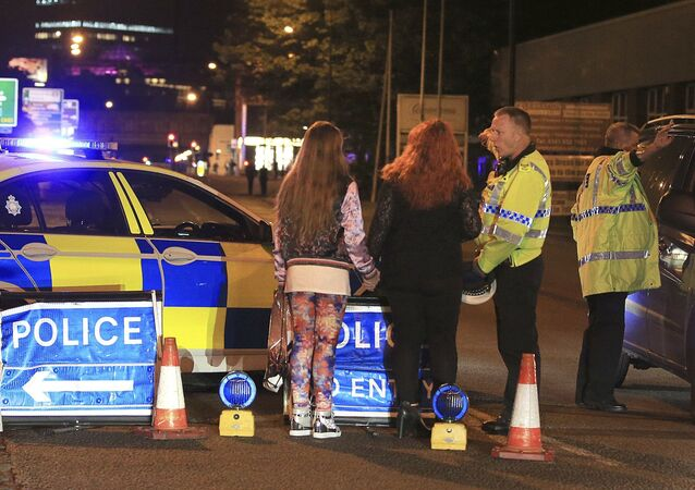 Police speak with concert goers at the Manchester Arena after reports of an explosion at the venue during an Ariana Grande concert.