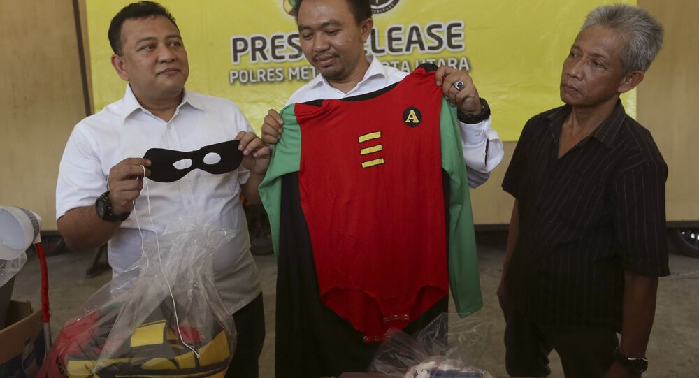Police officers show a costume confiscated in a raid on a gay sauna at North Jakarta police headquarters