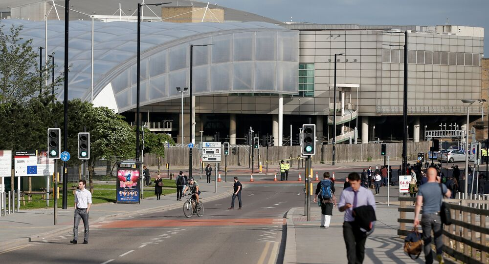 Commuters walk to work as a police cordon surrounds the Manchester Arena, Britain May 23, 2017.