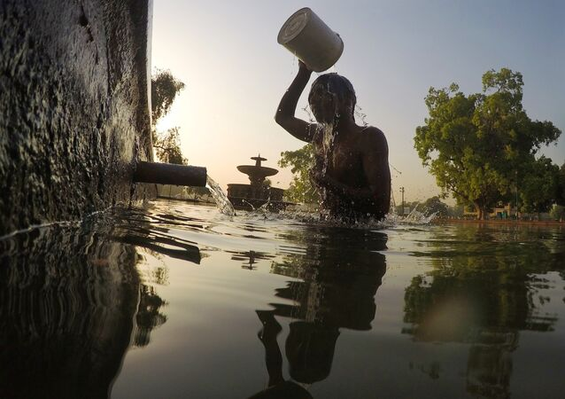 An Indian man bathes in a decorative pool in the gardens surrounding the India Gate monument in New Delhi on May 2, 2017.