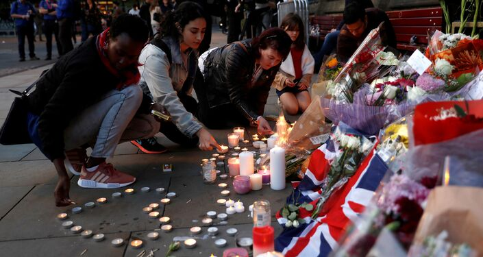 Women light candles for the victims of the Manchester Arena attack, in central Manchester, May 23, 2017.