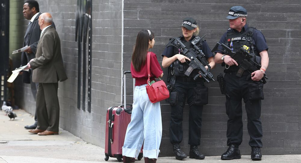 Armed police officers patrol amongst commuters on Market Street in Manchester, England, Wednesday, May 24, 2017.