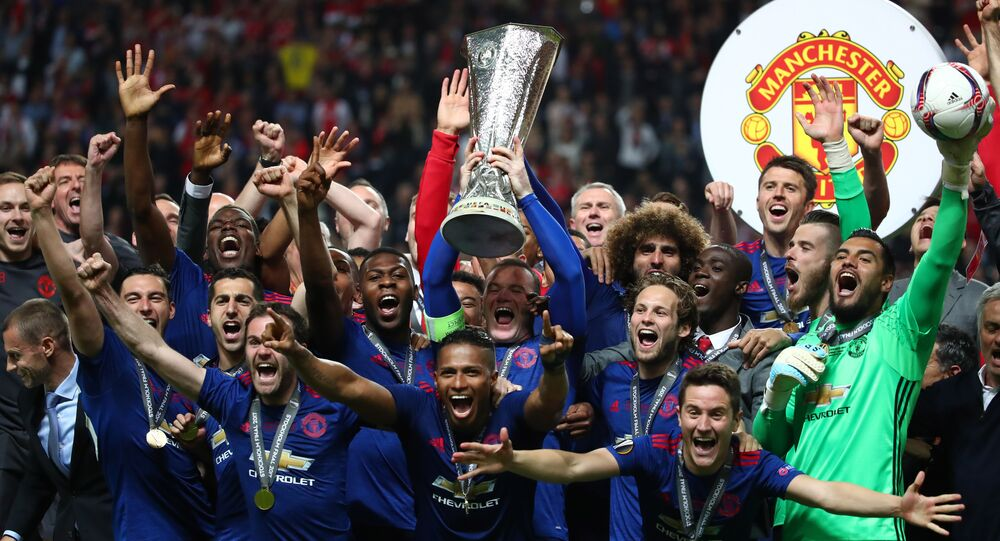 Manchester United's Wayne Rooney and team mates celebrate with the trophy after winning the Europa League