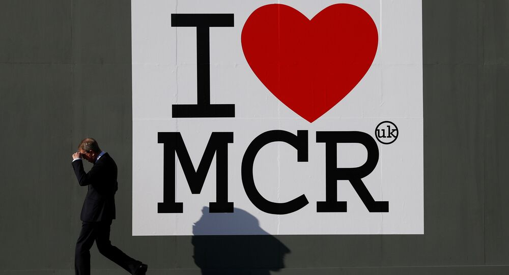 A man walks past a sign in central Manchester, Britain May 25, 2017.