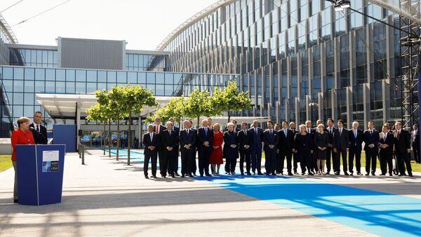 German Chancellor Angela Merkel (L) speaks beside NATO Secretary General Jens Stoltenberg and NATO members leaders at the start of the NATO summit at their new headquarters in Brussels, Belgium - Sputnik International