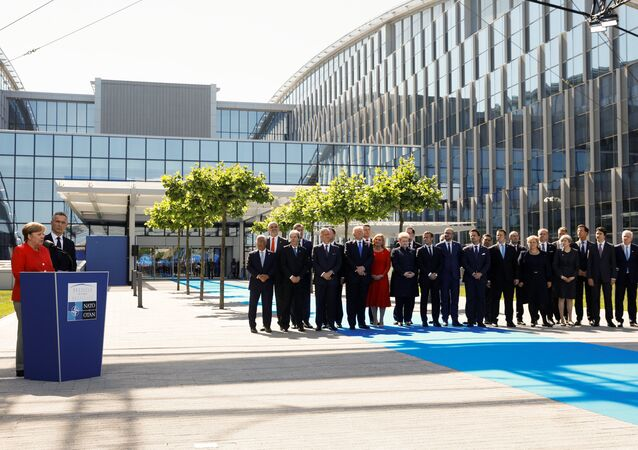 German Chancellor Angela Merkel (L) speaks beside NATO Secretary General Jens Stoltenberg and NATO members leaders at the start of the NATO summit at their new headquarters in Brussels, Belgium