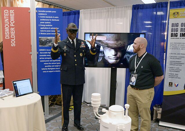 Maj. Gen. Cedric Wins, commanding general of the US Army Research, Development and Engineering Command, uses hand motions in an augmented reality demo under the guidance of ECBC Animation Team Lead Jason Gitlin.