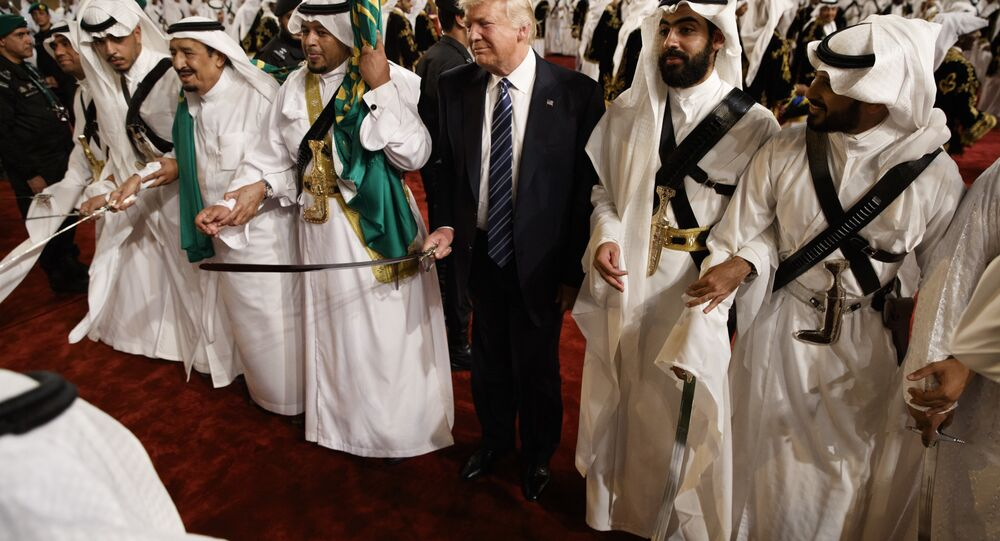 President Donald Trump holds a sword and sways with traditional dancers during a welcome ceremony at Murabba Palace in Riyadh