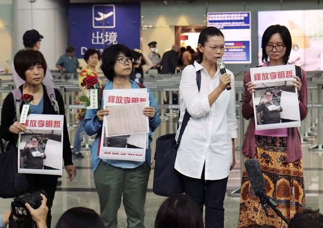 Li Ching-yu, center right, wife of Taiwanese pro-democracy activist Li Ming-che detained in China, gives a press conference after she was denied boarding the flight to Beijing at the airport counter at Taoyuan international airport in Taoyuan, Taiwan Monday, April 10, 2017.