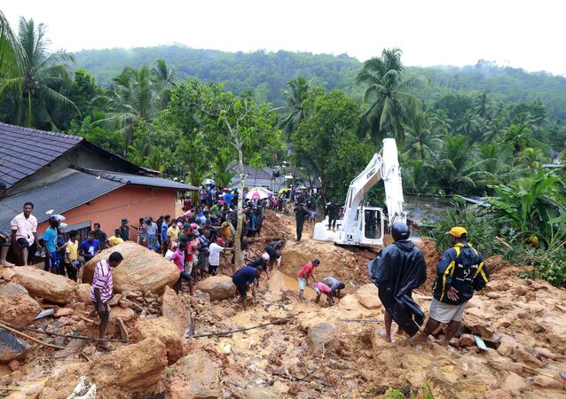 Sri Lankans watch military rescue efforts at the site of a landslide at Bellana village in Kalutara district, Sri Lanka, Friday, May 26, 2017.