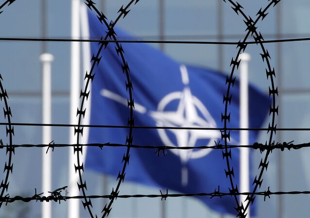 The NATO flag is seen through barbed wire as it flies in front of the new NATO Headquarters in Brussels, Belgium.