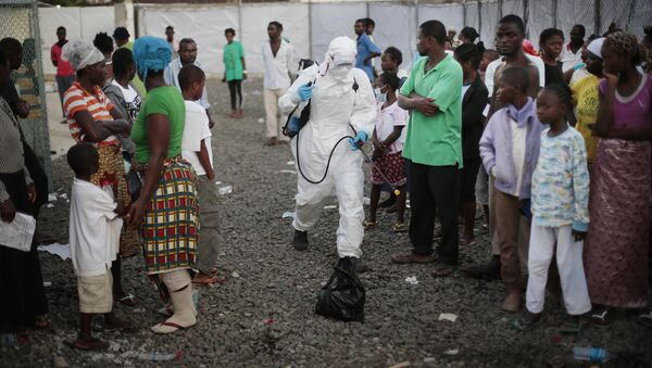 In this file photo daetd Tuesday, Sept. 30, 2014, a medical worker sprays people being discharged from the Island Clinic Ebola treatment center in Monrovia, Liberia - Sputnik International