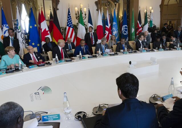 German Chancellor Angela Merkel, rear left, and and U.S. President Donald Trump, rear third left, attend a round table meeting of G7 leaders and Outreach partners at the Hotel San Domenico during a G7 summit in Taormina, Italy, Saturday, May 27, 2017