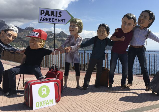 Oxfam activists wearing masks of the leaders of the G7 summit; from left, Italian Premier Paolo Gentiloni, US President Donald Trump, German Chancellor Angela Merkel, Japanese Prime Minister Shinzo Abe, French President Emmanuel Macron and Canadian Prime Minister Justin Trudeau, stage a demonstration in Giardini Naxos, near the venue of the G7 summit in the Sicilian town of Taormina, southern Italy, Friday, May 26, 2017