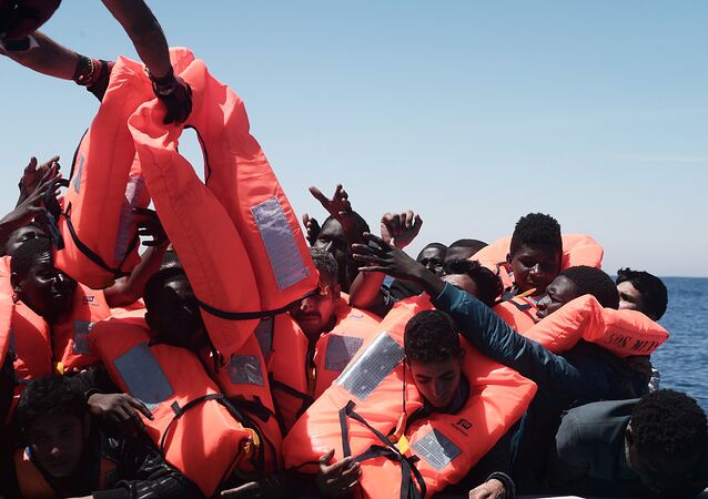 Migrants in an overcrowded plastic raft reach out for life jackets during a search and rescue operation by rescue ship Aquarius, operated by SOS Mediterranean and Doctors without Borders, in central Mediterranean Sea May 18, 2017