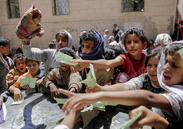 Yemenis present documents in order to receive food rations provided by a local charity, in Sanaa, Yemen, Thursday, April, 13, 2017