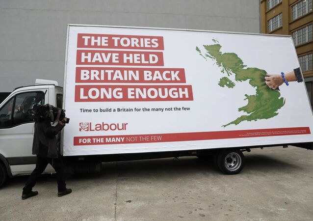 A cameraman films a poster unveiled by Britain's opposition Labour party for the upcoming general election, which their party leader Jeremy Corbyn did not attend, in London, Thursday, May 11, 2017