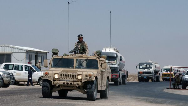 A convoy of fuel tanker trucks escorted by a US Army vehicle enter Kuwait at the military border post of Abdaly in the Kuwait-Iraq frontier in this file photo taken January 2006 - Sputnik International