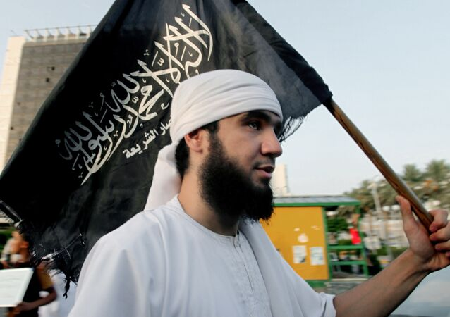 Libyan follower of Ansar al-Shariah Brigades chants as he carries the Brigades flag (File)