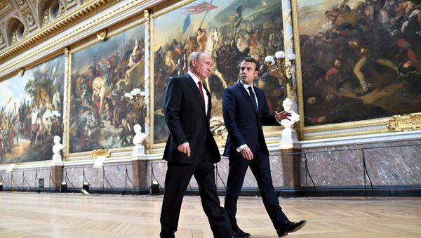 French President Emmanuel Macron (R) speaks to Russian President Vladimir Putin (L) in the Galerie des Batailles (Gallery of Battles) as they arrive for a joint press conference at the Chateau de Versailles before the opening of an exhibition marking 300 years of diplomatic ties between the two countries in Versailles, France, May 29, 2017 - Sputnik International