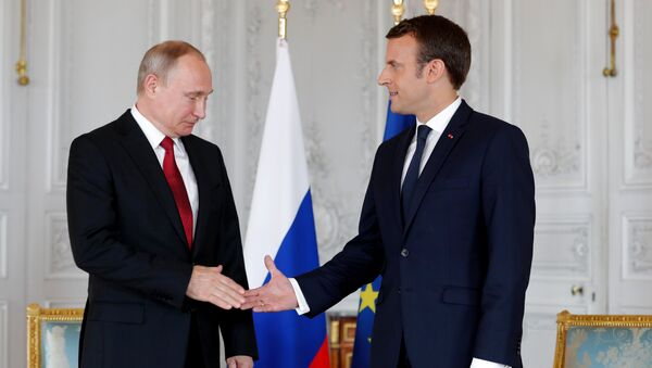 French President Emmanuel Macron shakes hands Russian President Vladimir Putin (L) at the Chateau de Versailles as they meet for talks before the opening of an exhibition marking 300 years of diplomatic ties between the two countyies in Versailles, France, May 29, 2017 - Sputnik International