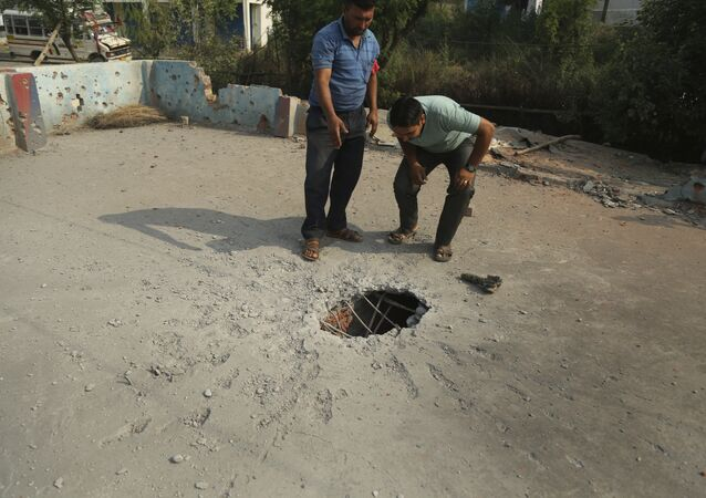 Indian civilians inspect the rooftop of a house damaged by mortar shells allegedly fired from the Pakistan side of the border, at a residential area near the Line of Control at the India Pakistan border at Jhanghar village, in Nowshera, India, Sunday, May 14,2017
