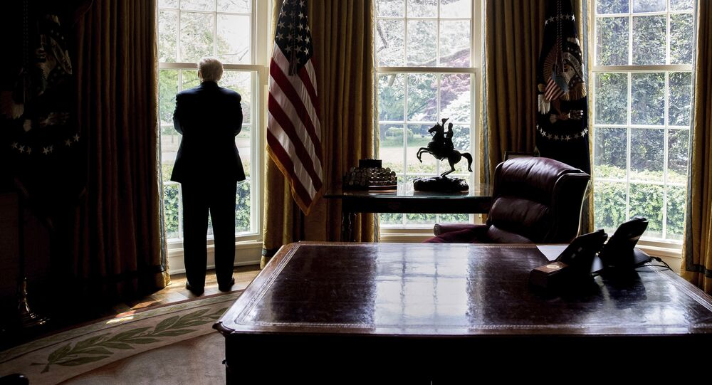 In this photo taken April 21, 2017, President Donald Trump looks out an Oval Office window at the White House in Washington following an interview with The Associated Press