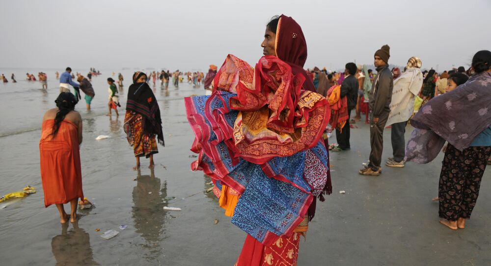 A woman holds saris of companions taking holy dips at the confluence of the Bay of Bengal and Ganges River on Makar Sankranti festival in Gangasagar, India, Saturday, Jan. 14, 2017
