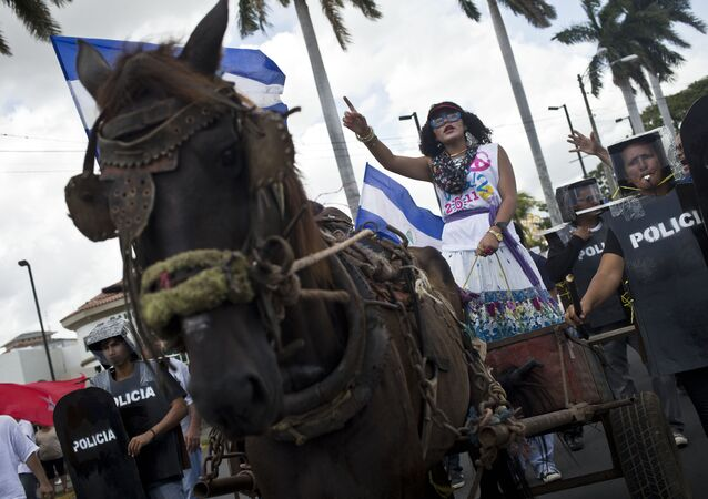 An anti-government protester dressed in the likeness of Nicaragua's first lady Rosario Murillo, navigates a chariot accompanied by a protective cordon of fellow protesters dressed as riot police, in a performance during a demonstration near the Supreme Electoral Council, where anti-government protesters gather every Wednesday demanding fair elections in 2016, in Managua, Nicaragua, Wednesday, Aug. 26, 2015