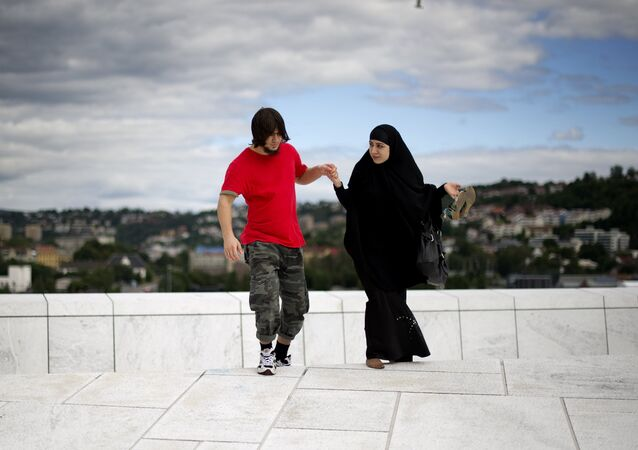 A man helps a woman up a step on the roof of the Opera house in Oslo