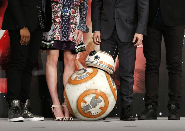 BB-8 droid poses with actors and director during a press conference for their latest film Star Wars: The Force Awakens at a hotel in Urayasu, near Tokyo Friday, Dec. 11, 2015.