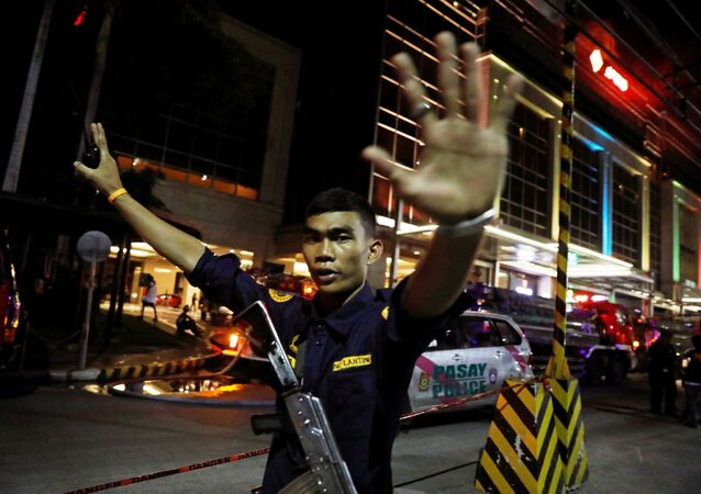 A security guard stops photographers from entering the vicinity of Resorts World Manila after gunshots and explosions were heard in Pasay City, Metro Manila, Philippines June 2, 2017.