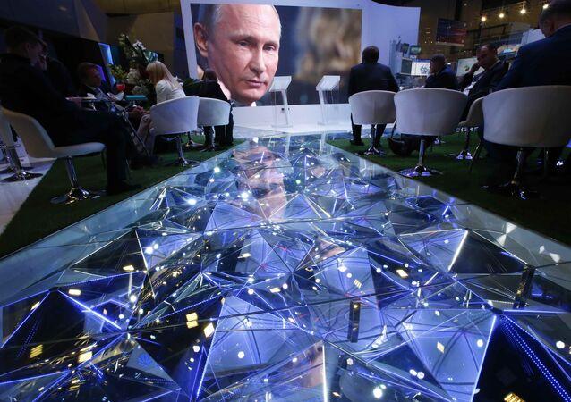 Participants of the St. Petersburg International Economic Forum (SPIEF) sit near an electronic screen showing Russian President Vladimir Putin, who attends a session of the forum in St. Petersburg, Russia, June 2, 2017