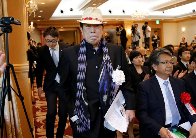 APA Group CEO Motoya holding his book, arrives at a news conference on publication of his book in Tokyo