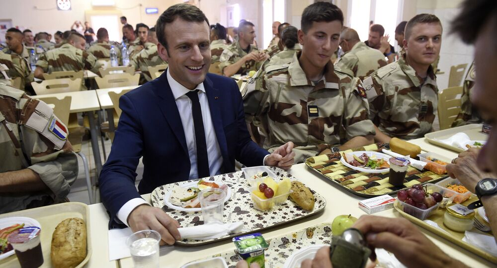 French President Emmanuel Macron (C) has a lunch break with French troops during his visit to France's Barkhane counter-terrorism operation in Africa's Sahel region in Gao, northern Mali, on May 19, 2017.
